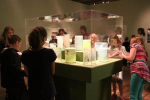 Visitors to Museum of Glass enjoying Irish Cylinders by Dale Chihuly and Seaver Leslie with Drawings by Flora C. Mace, 2013-14.
