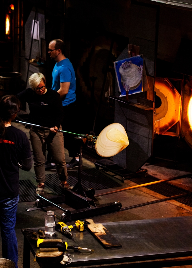 Hot Shop Team member Sarah Gilbert transfers the piece from the bench, where the artists are working, to the gloryhole for it to be heated back up to above 900 degrees Fahrenheit. This is important to keep the glass from cooling too quickly and cracking.