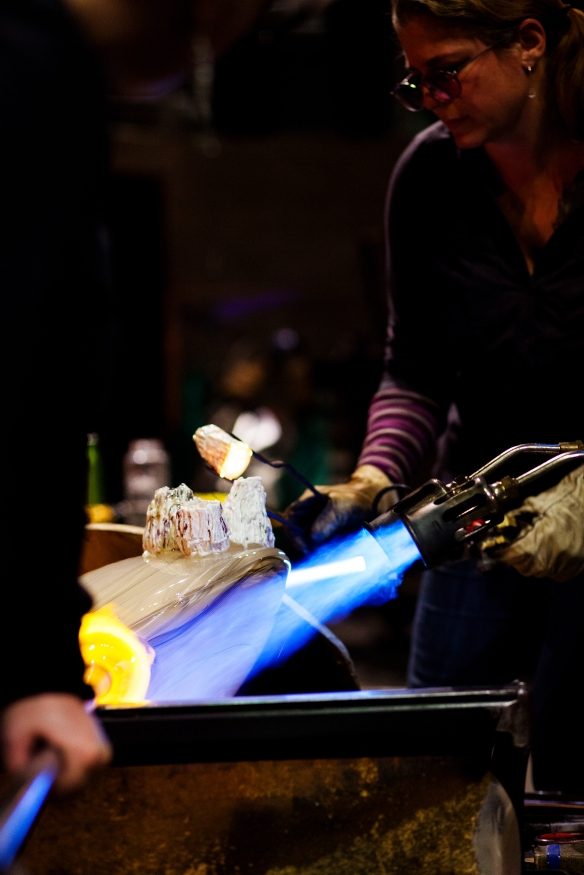 Kelly O'Dell attaches a heated barnacle to the clamshell using a pair of tweezers. A torch is being used to keep the rest of the glass at the same temperature. Kelly also has a torch which she is using to heat the bottom of the barnacle so the hot glass can stick to the surface of the clamshell.