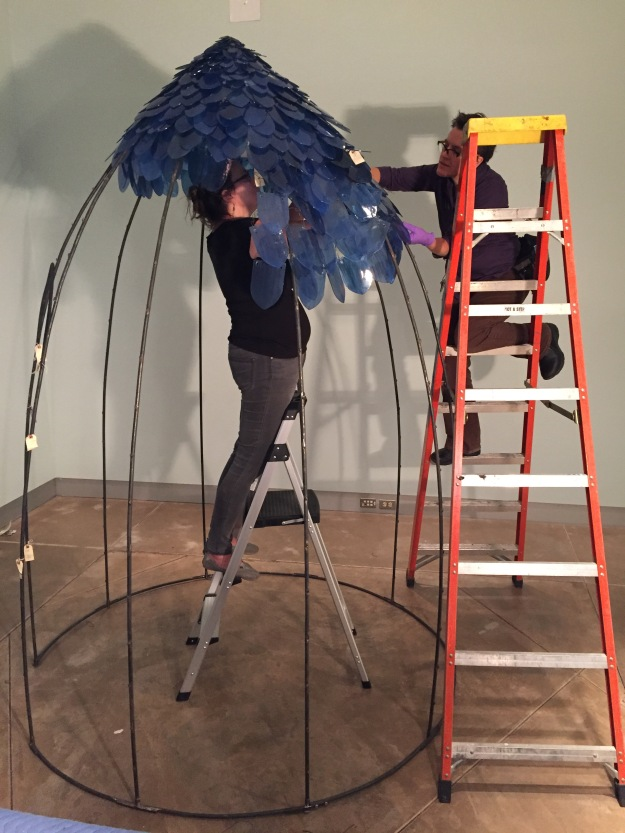 Artist Kait Rhoads (in center of dome) works with MOG art handler Elizabeth Mauro to connect a section of glass scales to the steel frame. On the left of the frame, you can see small tags that are used to mark the connection points for the sections of scales.