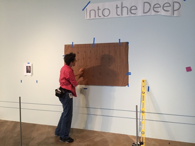 MOG art handler Elizabeth Mauro marks the template for on the wall. By hanging the template on the wall using a level, she is able to push a nail through the paper template, leaving a mark on the wall where each mount needs to be attached.