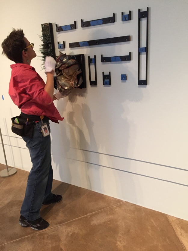 After all of the french cleats are attached to the wall, we can hang each of the frames. Here, Elizabeth is wearing gloves to keep the glass clean.